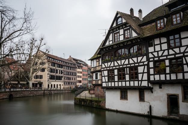 Rzeka Otoczona Kolorowymi Budynkami I Zielenią Pod Zachmurzonym Niebem W Strasburgu We Francji Darmowe Zdjęcia