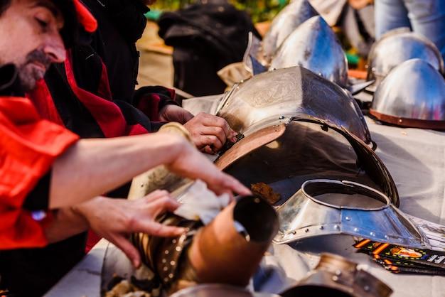 Rzemieślnicy Przebrani Za Epokę średniowieczną Nagniatają Brudną Zbroję, By Je Oczyścić. Premium Zdjęcia