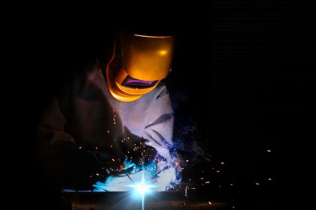 Rzemieślnik spawa stalą przedmiotu obrabianego osoba pracująca o stali spawacza korzystanie ze spawarki elektrycznej w fabryce występują linie światła i sprzęt bezpieczeństwa. Premium Zdjęcia