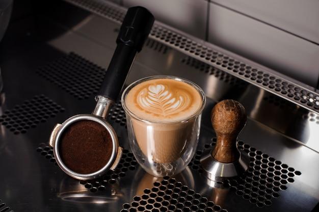 Sabotaż i filiżanka kawy wypełnione dekorowanym latte na blacie Premium Zdjęcia
