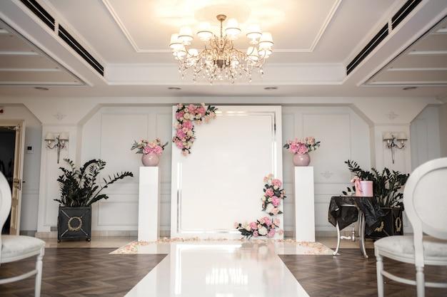 Sala weselna. rzędy białych świątecznych krzeseł dla gości. łuk ślubny dla pary młodej. Premium Zdjęcia