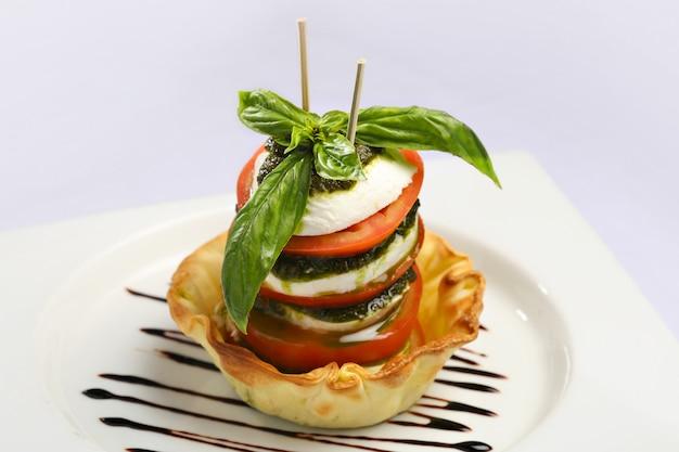 Sałatka caprese, sałatka włoska. plastry pomidora i świeżej mozzarelli oraz liście bazylii z oliwą z oliwek. Premium Zdjęcia
