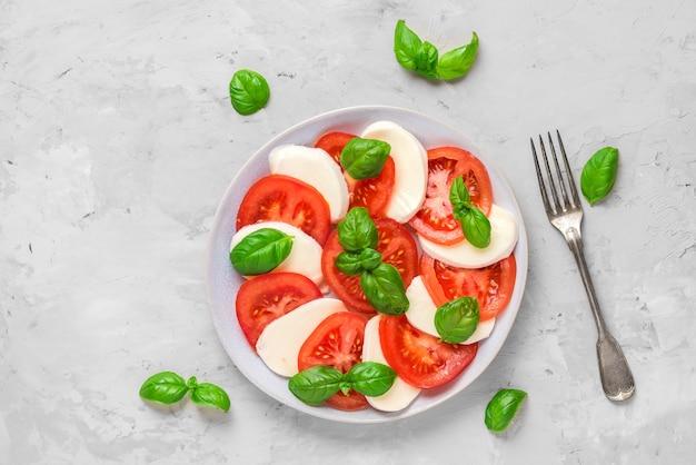 Sałatka Caprese Z Dojrzałymi Pomidorami I Serem Mozzarella, świeżymi Liśćmi Bazylii I Widelcem. Włoskie Jedzenie Premium Zdjęcia