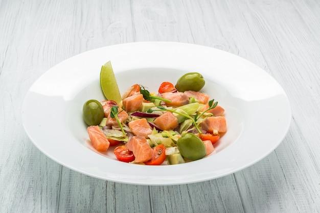 Sałatka Makaronowa Z Wędzonym łososiem, Oliwkami, Pomidorami Koktajlowymi, Różową Papryką I świeżą Bazylią Domowe Jedzenie Symboliczny Wizerunek Premium Zdjęcia