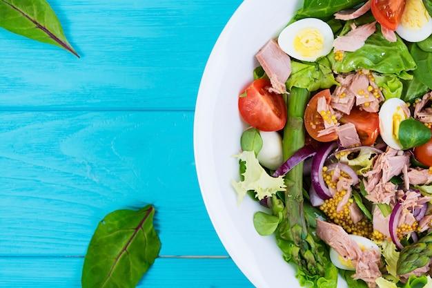 Sałatka Z Tuńczykiem, Pomidorami, Jajkami Przepiórczymi, Szparagami I Cebulą Na Drewnianym Premium Zdjęcia