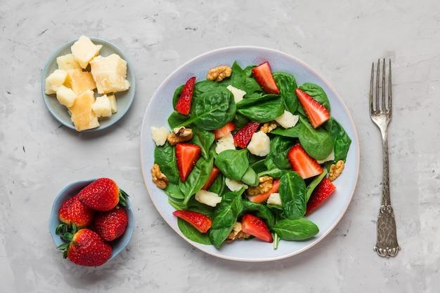 Sałatka Ze świeżych Truskawek Z Liśćmi Szpinaku, Parmezanem I Orzechami Włoskimi Z Widelcem. Zdrowa Dieta Ketonowa Premium Zdjęcia