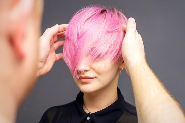 Salon Fryzjerski Sprawdzanie Krótkie Różowe Fryzury Młodej Kobiety Na Szarej ścianie Premium Zdjęcia