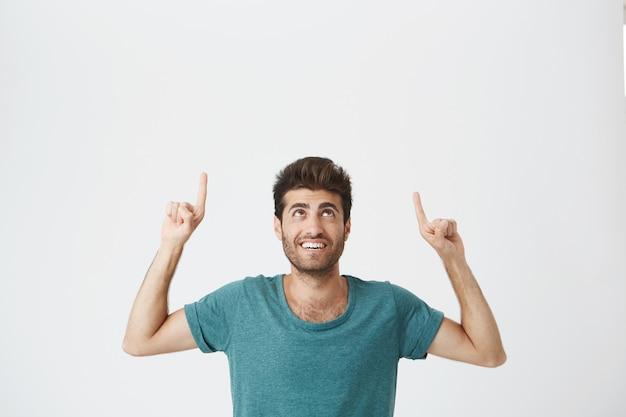 Salowy Portret Radosny Brodaty Hiszpański Facet Z Zadowolonym Wyrazem, Ubrany W Niebieski Tshirt, śmiejący Się I Wskazujący Do Góry Nogami Na Białej ścianie. Skopiuj Miejsce Darmowe Zdjęcia