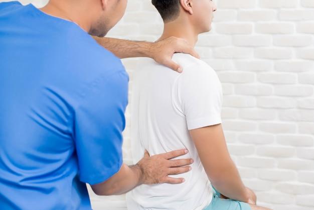 Samiec doktorski terapeuta leczy dolnego bólu pleców pacjenta w klinice lub szpitalu Premium Zdjęcia