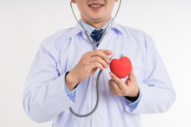 Samiec Lekarka W Bielu Munduru Chwyta I Use Stetoskopie Sprawdzać Up Kierowego Czerwieni Zabawki Serce. Premium Zdjęcia