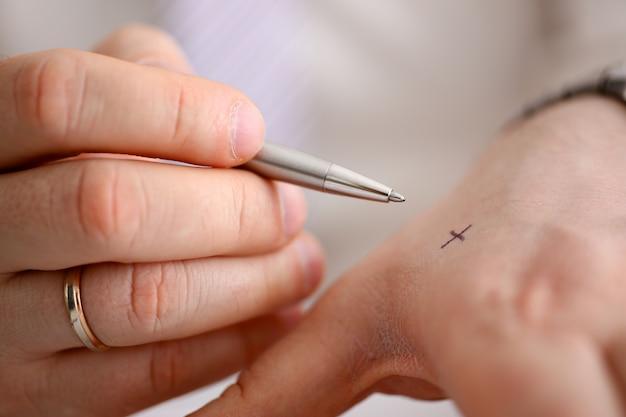 Samiec Robi X Krzyża Notatce Z Srebnym Piórem Przy Jego Ręką Dla Utrzymania W Pamięci W Biurowym Zbliżeniu. Staraj Się Nie Zapomnieć Zrobić Koncepcji Listy Premium Zdjęcia