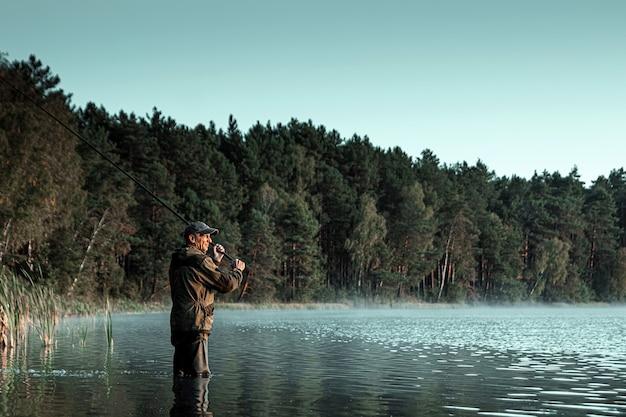 Samiec Rybak Na Jeziorze Stoi W Wodzie I łowi Wędkę Wędkarskie Wakacje Hobby Premium Zdjęcia