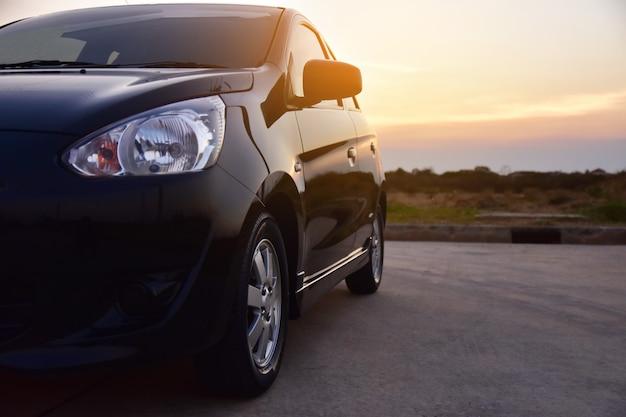 Samochód zaparkowany na drodze i mały fotelik samochodowy na drodze używanej do codziennych podróży Premium Zdjęcia