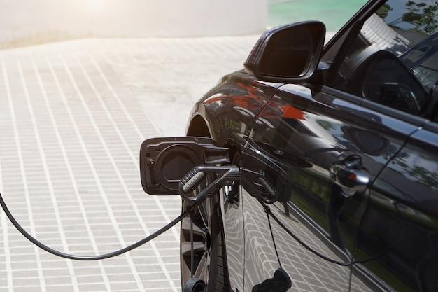 Samochody elektryczne ładują energię elektryczną do przechowywania w akumulatorach samochodowych. Premium Zdjęcia