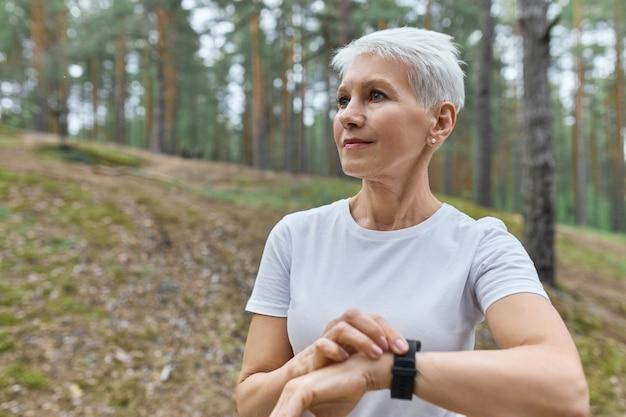 Samodzielna Sportsmenka W średnim Wieku W Białej Koszulce Dostosowuje Inteligentny Zegarek, Sprawdza Statystyki Fitness, Monitoruje Jej Wydajność Podczas Treningu Cardio W Parku Darmowe Zdjęcia