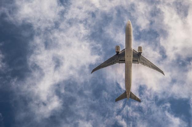 Samolot na niebieskim niebie z chmurami. podróżuj po świecie w powietrzu Premium Zdjęcia