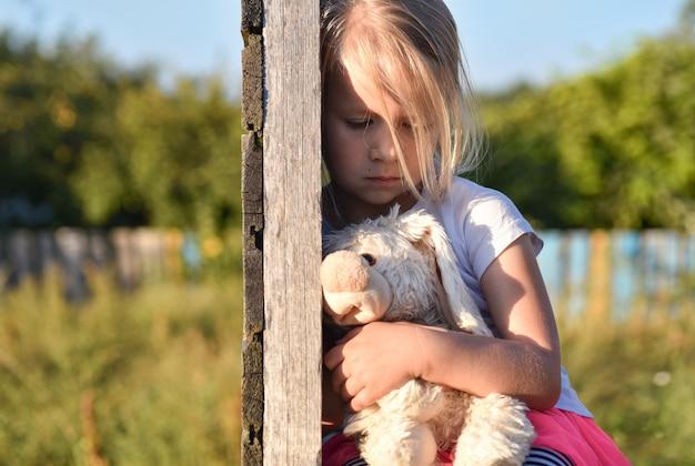 Samotna dziewczyna na ulicy jest smutna i trzyma zając zabawkowy rękami Premium Zdjęcia