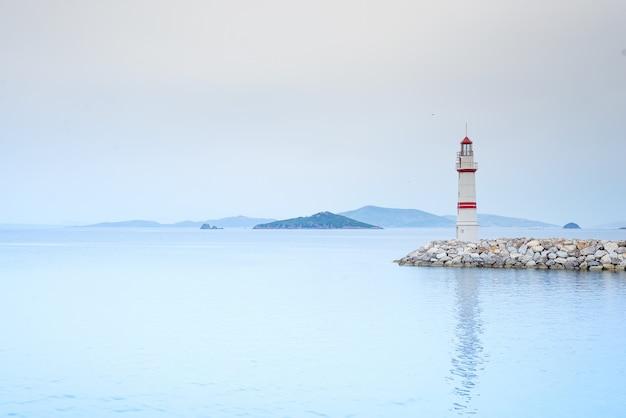 Samotna Latarnia Morska Na Kamiennej Drodze Pośrodku Morza Z Widokiem Na Góry I Mgłę Premium Zdjęcia