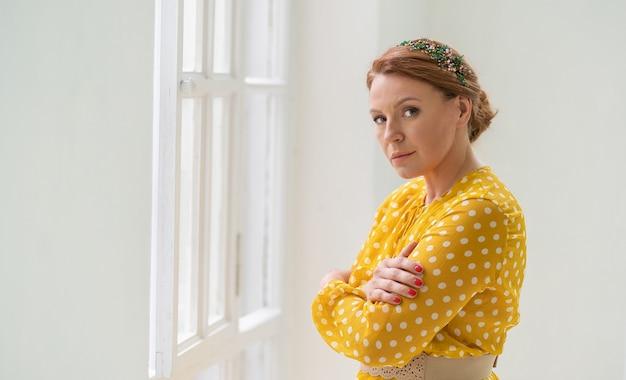 Samotna rudowłosa kobieta w żółtej sukience przytula się Premium Zdjęcia