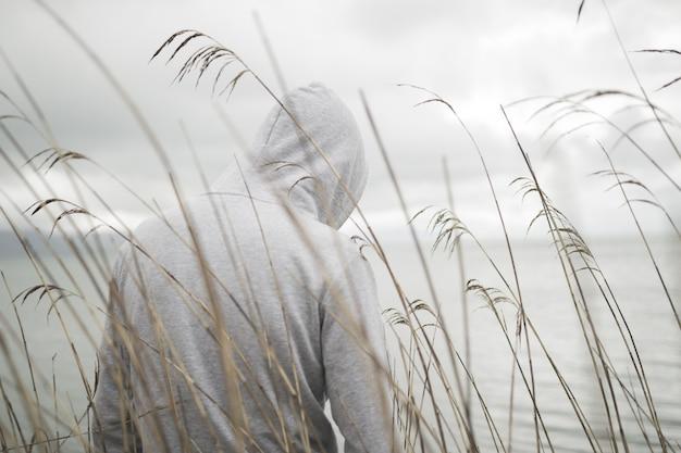 Samotna Smutna Osoba Od Tyłu W Bluzie Z Kapturem, Siedząca Nad Morzem Myśląca O życiu Darmowe Zdjęcia