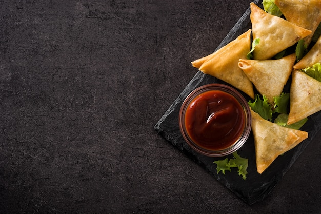 Samsa lub samosas z mięsem i warzywami na czarno. tradycyjne indyjskie jedzenie. przestrzeń kopii Premium Zdjęcia