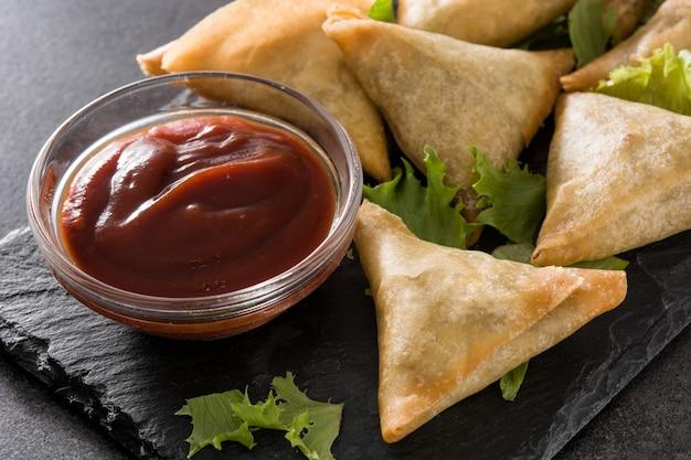 Samsa Lub Samosas Z Mięsem I Warzywami Na Czarno. Tradycyjne Indyjskie Jedzenie. ścieśniać Premium Zdjęcia