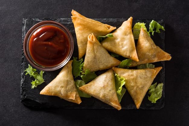 Samsa lub samosas z mięsem i warzywami na czarno. tradycyjne indyjskie jedzenie. Premium Zdjęcia