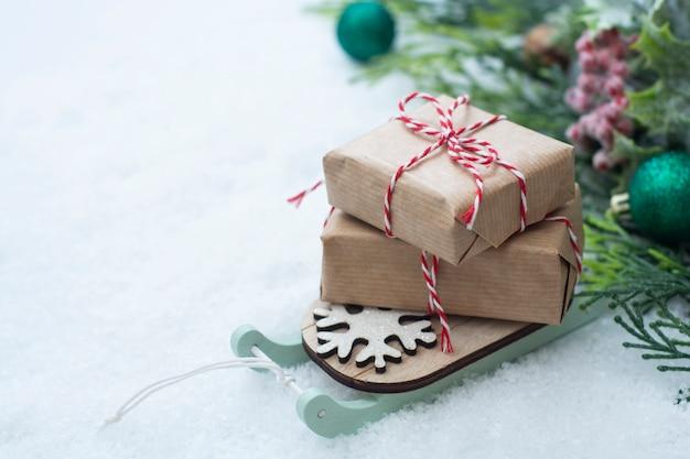 Sanie świąteczne z pudełka na śniegu. streszczenie zima kartkę z życzeniami. Premium Zdjęcia