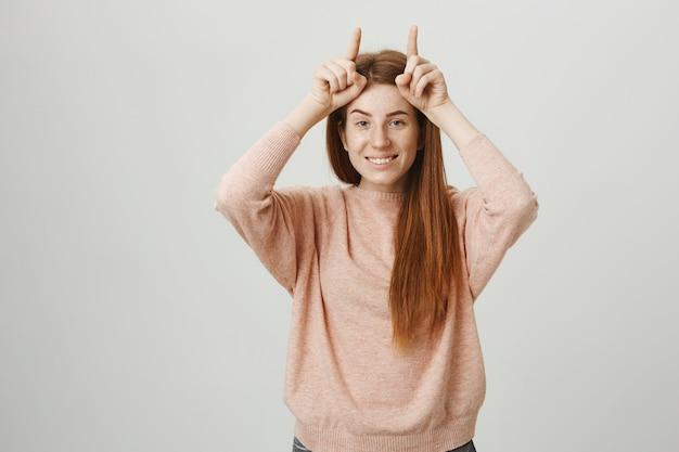 Sassy śliczna Ruda Dziewczyna Pokazująca Diabelskie Rogi Na Głowie Darmowe Zdjęcia