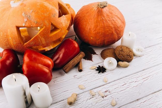 Scarry Halloween Dynia Stoją Na Stole Z świece, Cynamon, Czerwony Pieprz I Orzechy Darmowe Zdjęcia