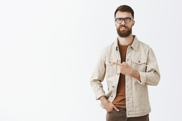 Sceptyczny I Zawiedziony Brodaty Mężczyzna W Okularach Pozujący Pod Białą ścianą Darmowe Zdjęcia