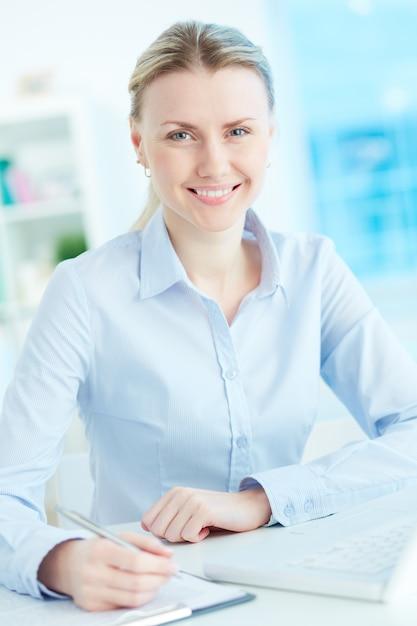 Sekretarz uśmiechnięta pisanie notatki Darmowe Zdjęcia