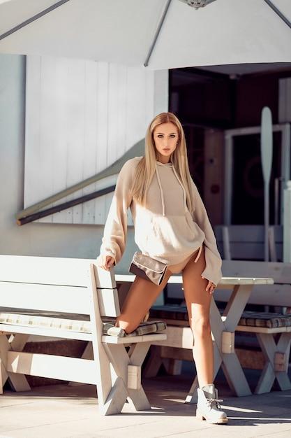 Seksowna blondynka w beżowej bieliźnie i płaszczu pozowanie w pobliżu kawiarni. odpoczynek i przyjemność. Premium Zdjęcia