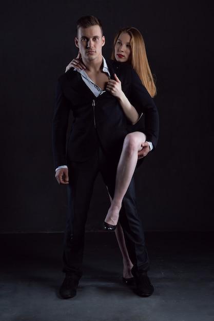 Seksowna Dziewczyna W Czarnej Sukni Zarzuciła Nogę Na Swojego Mężczyznę Premium Zdjęcia