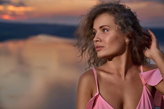 Seksowna Dziewczyna Z Kręconymi Włosami W Różowej Sukience Z Odkrytymi Ramionami. Premium Zdjęcia
