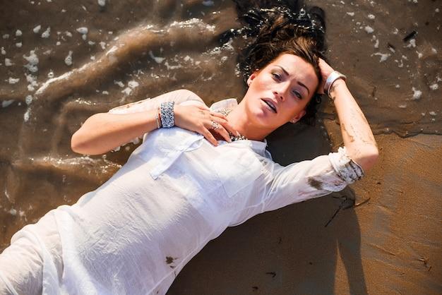Seksowna I Piękna Kobieta Kłama W Mokrym Piasku Na Plaży Premium Zdjęcia