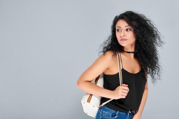 Seksowna Młoda Dziewczyna Z Czarnymi Kręconymi Włosami, Niosąca Biały Plecak Ze Złotym Zamkiem. Nosi Czarny Jasny Top I Niebieskie Dżinsy. Darmowe Zdjęcia