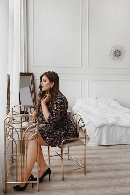Seksowna Modelka Plus Size Siedzi Przy Toalecie I Patrzy W Lustro. Młoda Tłuściuchna Kobieta Z Jaskrawym Makeup W Smokingowym Przygotowaniu Do świętowania. Gruba Kobieta W Modnym Stroju. Moda Xxl. Premium Zdjęcia