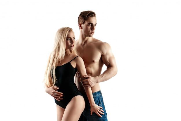 Seksowna Para, Mięśniowy Mężczyzna Trzyma Pięknej Kobiety Odizolowywającej Na Białym Tle Premium Zdjęcia