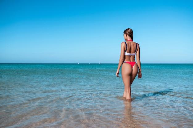 Seksowny Plecy Piękna Kobieta W Czerwonym Bikini Na Dennym Tle Premium Zdjęcia
