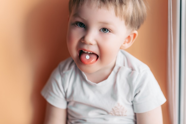 Selektywne focus na białą pigułkę na języku małego chłopca malucha Premium Zdjęcia