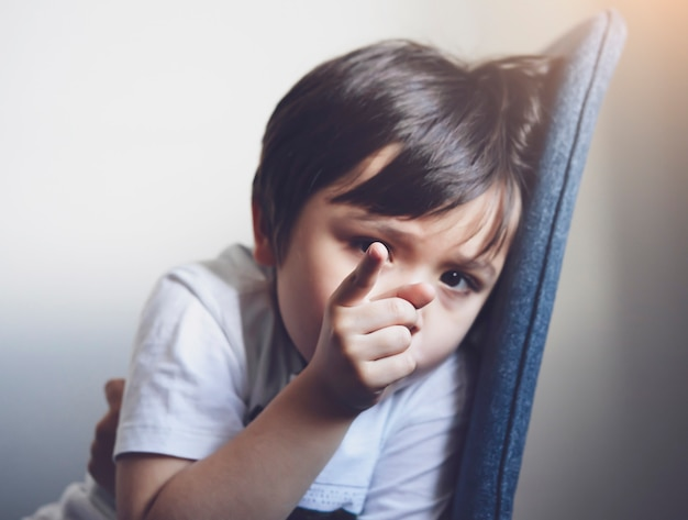 Selektywny Fokus Mały Chłopiec Siedzi Na Krześle, Wskazując Palcem Na Aparat, Szczery Brak Chłopca Ze Szkoły Podstawowej, Wskazując Na Ciebie Palcem, Zepsute Dzieci Koncepcja Premium Zdjęcia