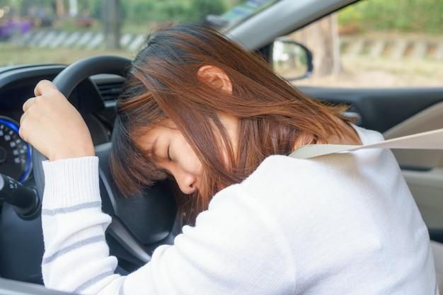 Sen, zmęczony, blisko oczy młoda kobieta jazdy jej samochodem po długiej podróży godzin Premium Zdjęcia