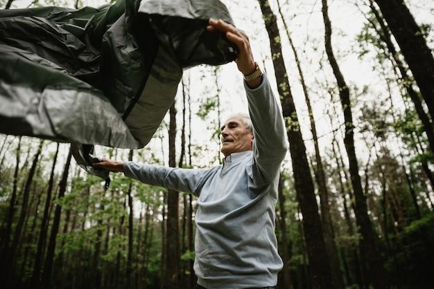 Senior Para Cieszy Się Wakacjami I Rozbija Namiot. Dorośli Spędzają Wakacje Na łonie Natury I Rozbijają Namiot. Seniorzy Biwakują I Rozkładają Namiot Premium Zdjęcia