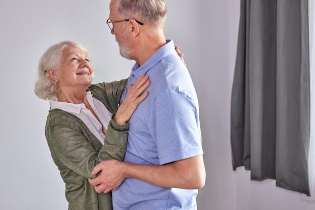 Senior Para Tańczy W Salonie, Mąż Trzymający Rękę Dojrzałej żony Ciesząc Się Wspólną Zabawą, Spędzać Wakacje, Emeryturę W Czasie Wolnym Lub Styl W Domu. W Codziennym Stroju Domowym Premium Zdjęcia