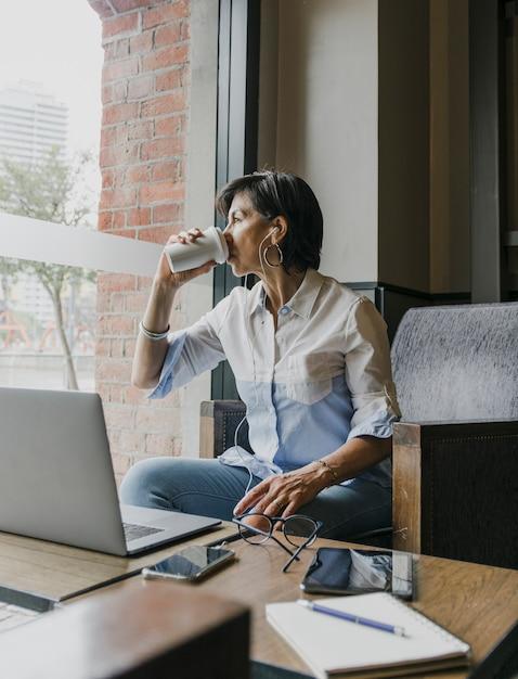 Senior pije kawę w jej biurze Darmowe Zdjęcia