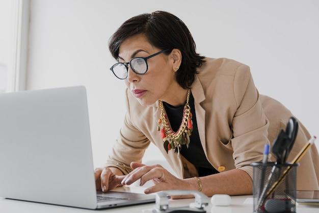 Senior pracuje na laptopu środka strzale Darmowe Zdjęcia