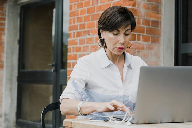 Senior siedzi na zewnątrz z laptopem Darmowe Zdjęcia