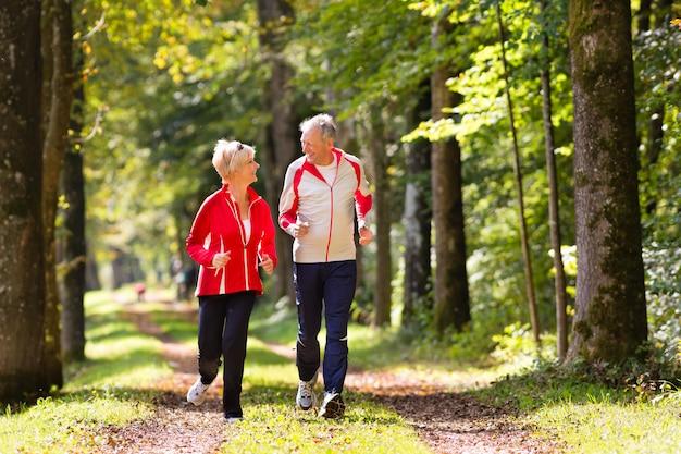 Seniorzy jogging na leśnej drodze Premium Zdjęcia