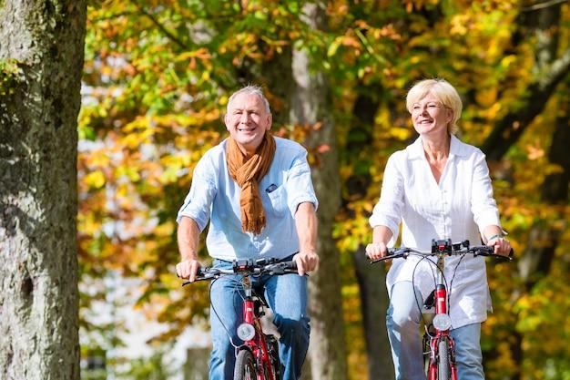Seniorzy na rowerach po wycieczce w parku Premium Zdjęcia